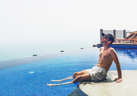 Side view of young man on vacation dangling legs in infinity swimming pool