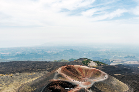 One of the lateral cones and crater, Mount Etna, Sicily , Italy with tourists on the rim sightseeing viewed from above