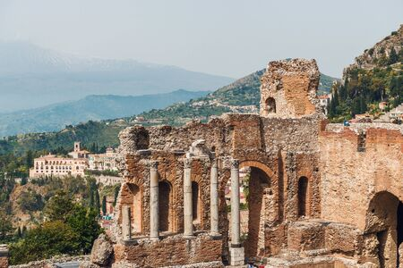 The ruins of the ancient Greek Theatre in Taormina on an elevated hilltop above the popular tourist resort in Sicily, Italy