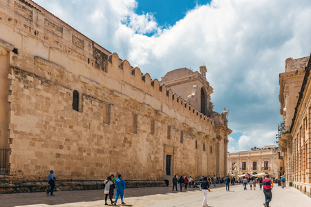SYRACUSE, SICILY, ITALY - APRIL 26, 2017: Tourists on main square piazza Duomo in Syracuse city in Sicily. The city is a historic town in Sicily, the capital of the province of Syracuse