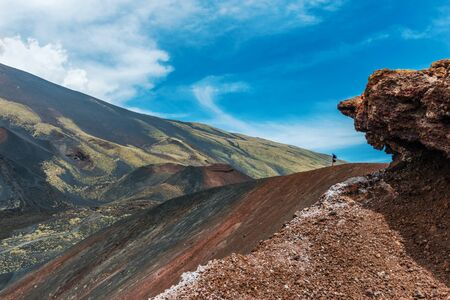 Landscape of Mount Etna Volcano with sightseers walking in background, Sicily