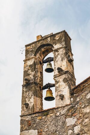 Bell tower on old colonial style church building with sky background