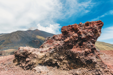 Lava rock formation on Mount Etna volcano with cloudscape background Stock Photo