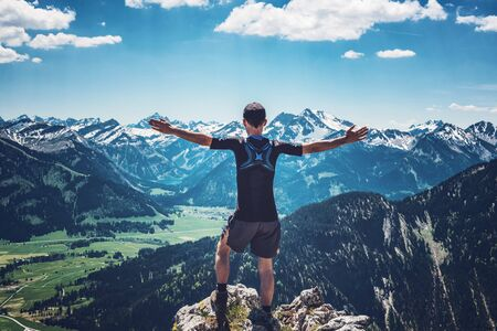 Hiker celebrating nature and reaching the summit after a trek