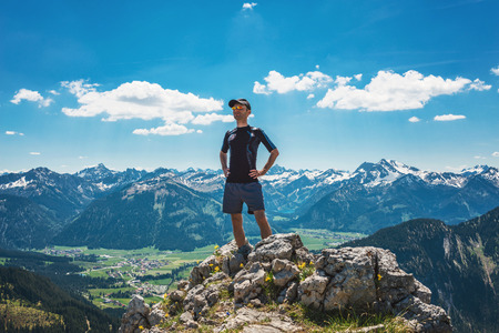 Successful and confident hiker on mountain summit with his hands on his hips
