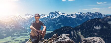 Man sitting on mountain summit, relaxing and enjoying nature. Banner