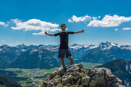 freedom: Powerful male hiker on mountain summit enjoying nature with his arms spread away