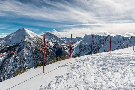 mountainous: Ski tracks leading to the edge of an alpine plateau with a line of red demarcation poles overlooking a vista of snow-capped mountain peaks and valleys Stock Photo