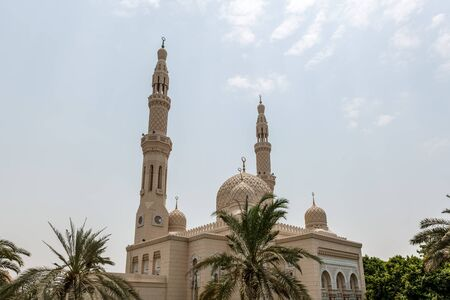 Architectural Exterior of Fatimid Style Jumeirah Mosque Surrounded by Palm Trees in Dubai City, United Arab Emirates on Sunny Day with Blue Sky