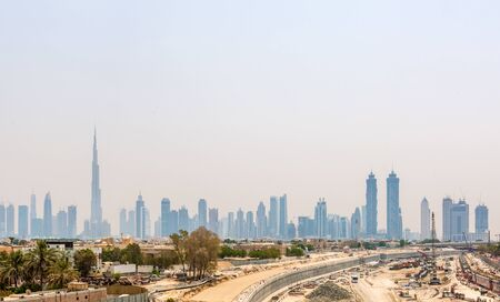 晴れた日にドバイ、アラブ首長国連邦の超高層ビルのブルジュ ・ ハリファによって支配される漠然とした街並み 写真素材
