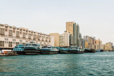 Water canal view of Arab city with several boats moored near traditional buildings - UAE