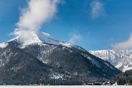 High altitude snow-capped mountains with forested slopes towering above the wooden chalets of a ski resort with white fluffy clouds clinging to the summit Lizenzfreie Bilder