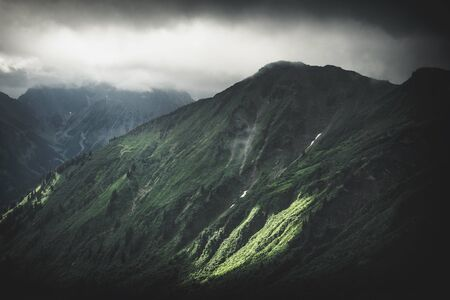 A panoramic view of a moody storm passing over a dramatic mountain range and rugged landscape.