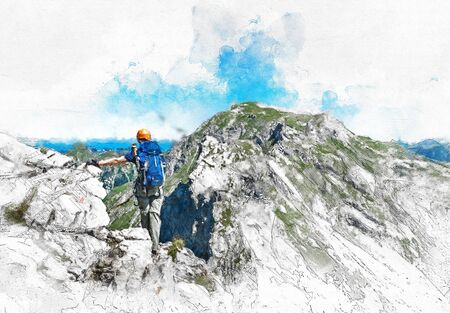 Mountain climber standing on the summit of a high alpine peak looking out over the vista of rugged mountains below and a saddle or ridge to cross with his back to the camera