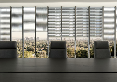 board: Empty chairs at desk in office room against partly covered windows with cityscape in background