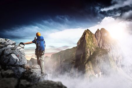 Hiker with backpack reaches the summit of a mountain peak during sunset. Success, freedom and happiness, achievement in mountain. Active sport concept.