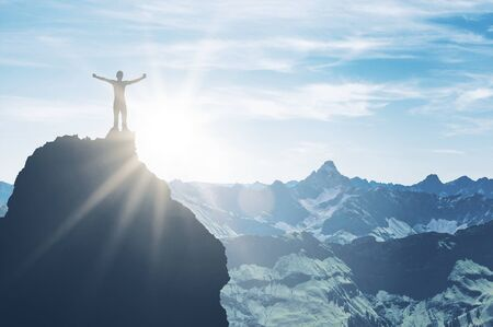 A triumphant mountaineer standing on a pinnacle embraces the bright morning sun light with outstretched arms in a majestic mountain scene. Lizenzfreie Bilder