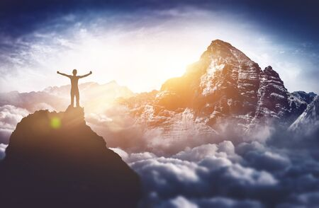A triumphant, silhouetted climber with a majestic mountain view raises their arms at sunrise from the summit of a tall mountain peak.