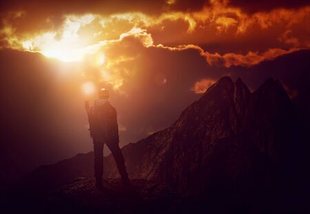A mountain climber on a peak with a majestic view is silhouetted by an intense, fiery red sunset.