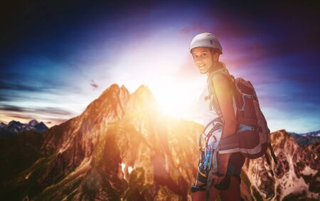 Fit athletic young woman out mountaineering standing in her gear backlit by the golden glow of the sun rising over a steep rocky mountain peak in a colorful sky turning to smile at the camera Lizenzfreie Bilder