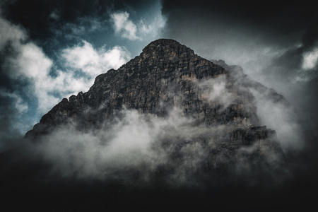 wispy: A dark, stormy fog shrouded rocky mountain peak towers above passing clouds. Stock Photo