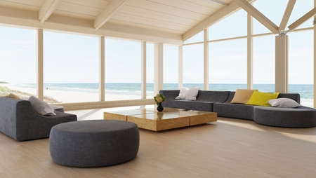 Modern luxury living room interior with wrap around glass walls overlooking the ocean and a large modular lounge suite on a hardwood floor. 3d render Archivio Fotografico