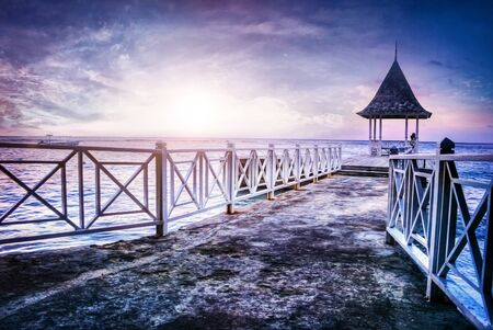 Tranquil scene of pier with gazebo against sea at sunrise