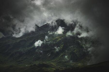 A dark, fog and cloud shrouded landscape with rugged mountain range and terrain. Lizenzfreie Bilder
