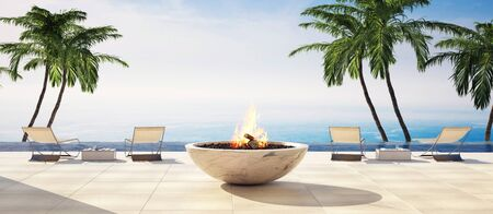 Luxury open air deck in a tropical villa with deck chairs overlooking palm trees and a calm ocean and burning central fireplace. 3d render Lizenzfreie Bilder