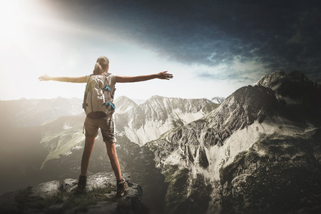 Mountain climber wearing a backpack standing on a rocky summit of an alpine peak looking out over the view of high alps and forested valleys on a cloudy blue sky day with vignette Lizenzfreie Bilder