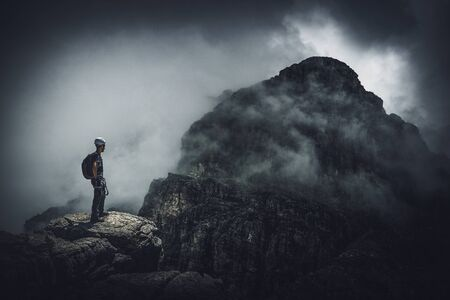 A mountain climber standing on a peak with a view over a dark, ominous, stormy mountain range. Lizenzfreie Bilder