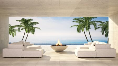 Luxurious waterfront tiled terrace with two empty comfortable white sofas and a fire pit against sea in an idyllic summer tropical destination