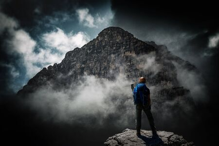 A mountain climber stands below a looming dark mountain peak shrouded in fog and cloud. Stock Photo