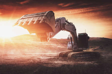 Large backhoe or digger with raised bucket at sunset backlit by a fiery sun as it stands in an industrial earth excavation site with sun flare