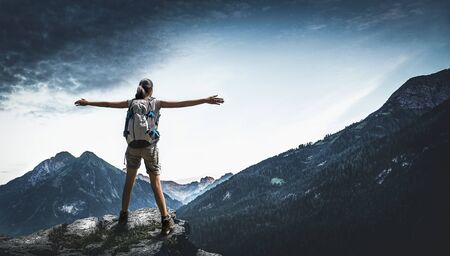 Rear view of female hiker spreading arms while standing on rock in mountains Lizenzfreie Bilder