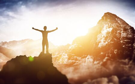 A successful, silhouetted climber with a majestic mountain view raises their arms at sunrise from the summit of a tall mountain peak. Stock Photo