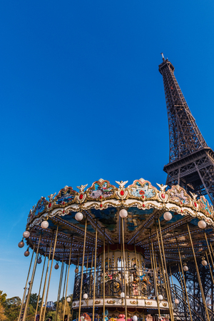 Low-angle view of a famous vintage carousel against Eiffel Tower, tourist attraction and famous landmark from Paris, France