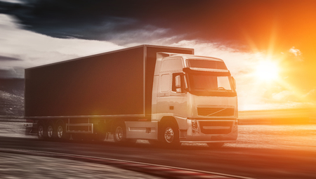 Large freight truck driving on a highway at sunset backlit by a bright orange sunburst under an ominous cloudy sky. 3d Rendering. Stock Photo