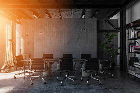 Bright, warm sunset light illuminates an industrial style polished concrete office with table and chairs.