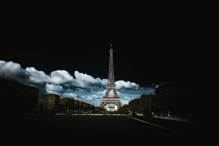 Eiffel Tower in darkness without the light display viewed across the park with dramatic white clouds and copy space for tourism and travel themes
