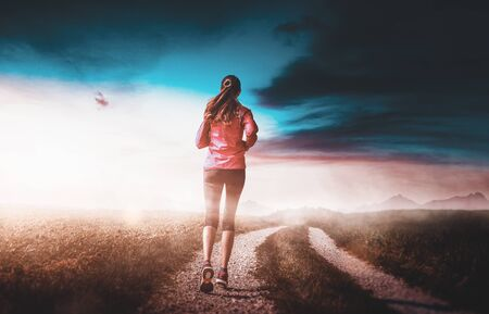 Woman jogging along a dirt road in countryside with an artistic colorful dawn sky with copy space in a health and fitness concept Stock Photo