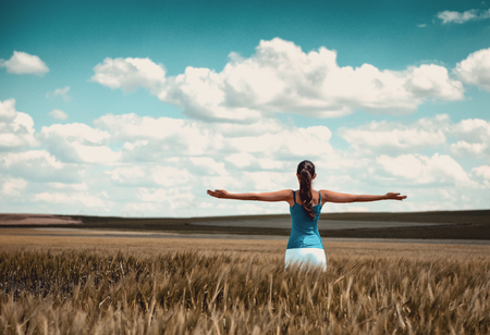 Woman standing in a corn field rejoicing with her back to the camera and arms outstretched as she faces the open countryside and cloudy blue sky