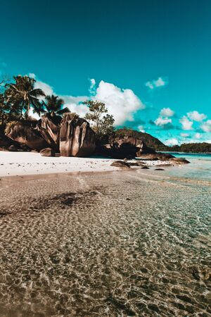 Idyllic Lazio Beach, Seychelles, viewed over sparkling rippling water with its unusual rock formations and palm trees