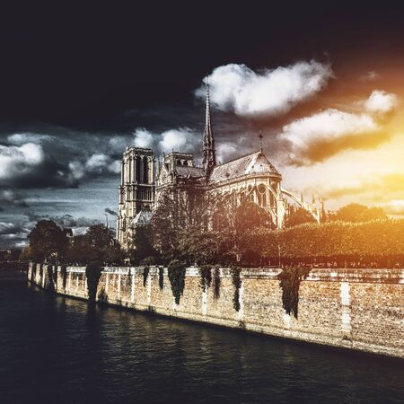Rear low-angle view of the right side of Notre-Dame de Paris cathedral against dramatic cloudy sky Standard-Bild