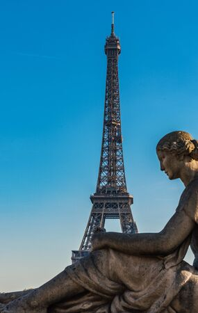 Eiffel Tower, Paris, France viewed against a sunny blue sky behind the statue of a seated woman in the foreground in a travel concept