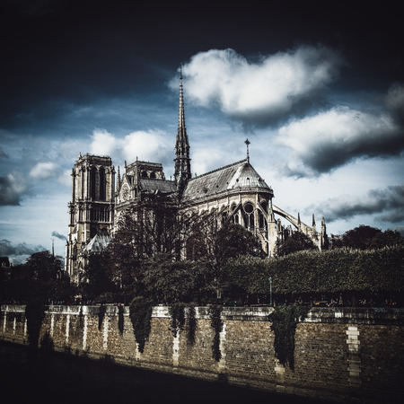 Right side view of Cathedral Notre-Dame de Paris against dramatic dark cloudy sky, tourist attraction in Paris, France