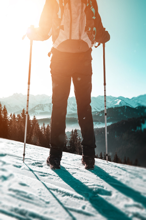 Rear view of hiker standing with poles against winter snowy mountains on sunny day