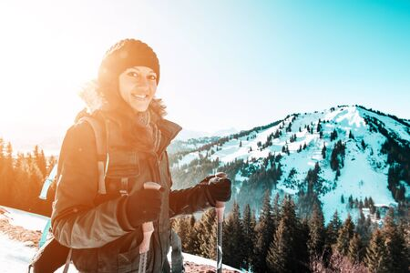Portrait of young smiling woman hiking in winter snowy mountains