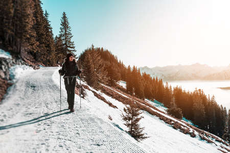 Woman hiking with poles along snowy trail in mountains on sunny day