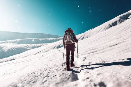 Rear view of person hiking in winter snowy mountains on sunny day